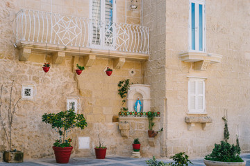Mdina, Malta. Narrow street of ancient city with maltese house built of limestone. The house decorated in catholic tradition