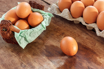 Eggs in a wattled basket on a wooden table, top view