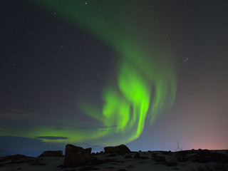 Northern lights, aurora over hills and tundra in the winter.
