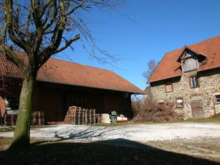 Gestapelte Holzpaletten auf einem schönen alten Bauernhof mit strahlend blauem Himmel in Heidenoldendorf bei Detmold in Ostwestfalen-Lippe