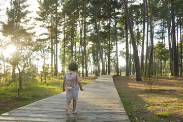 little girl walking on a path in the woods at sunset