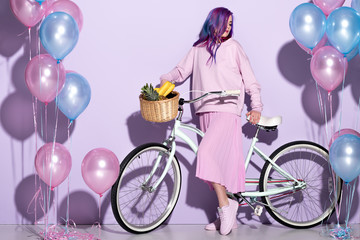 beautiful young woman in pink clothing on bicycle with pineapple and bananas in basket