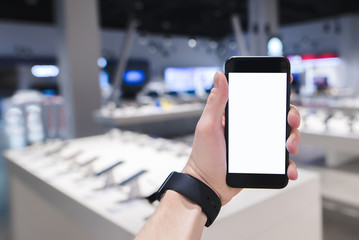 A person holds a smartphone in the background of a technology store. Phone against the background of a blurry store