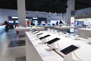 Many smartphones are on the table in the technology store. Buying a mobile phone at the electronics store. Smartphones on the background of the store