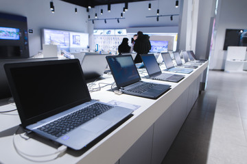 Laptops in a modern technology store. Department of computers in the electronics store. Choosing a laptop in the store