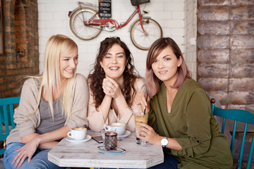 Photo of female friends drinking coffee together. Three young women at cafe smiling, laughing and having fun