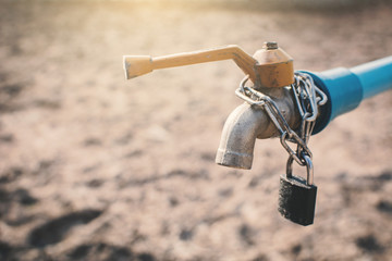 Key and chain locked faucet on cracked dry ground , concept drought and shortage of water
