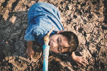Sad girl want to drink some water on crack ground , Concept drought and shortage of water crisis