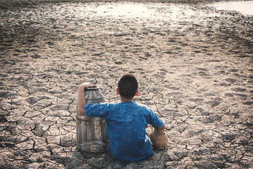 Sad boy tired and exhausted on cracked dry ground , Concept drought and shortage of water crisis