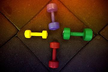 colored dumbbells on a black background
