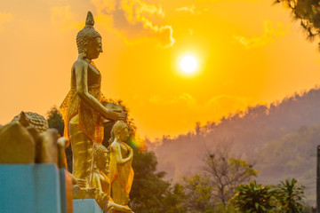scenery sunset behind the golden buddha statue at wat Sirattanan Mongkol near Mae Kajan Hot Spring. Wiang Pa Pao Chiang Rai Thailand.