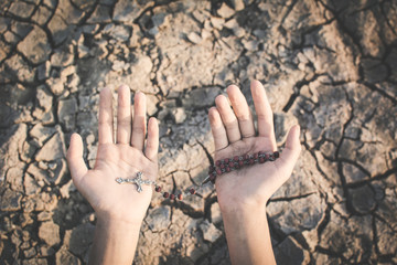 Human hands praying for the rain on cracked dry ground , Concept drought and shortage of water crisis, selective and soft focus
