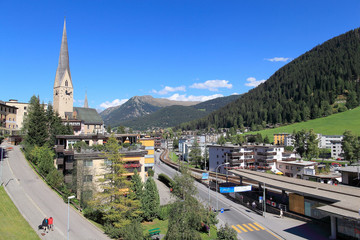 Summer view of beautiful Davos under blue clear sky. It is a famous Swiss skiing resort and hosts annual winter meeting of World Economic Forum (WEF).
