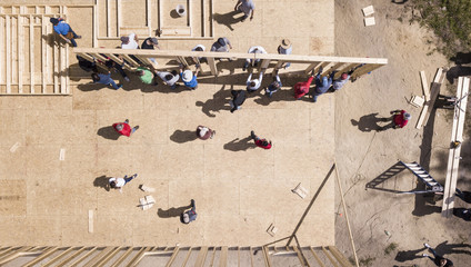 Top down view of workers raising a wall on construction of a new home.