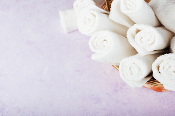 Rolled up white spa towels in a basket. Violet or purple marbel stone background.