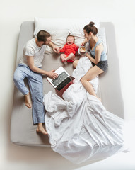 Top view of happy family with one newborn child in bedroom.