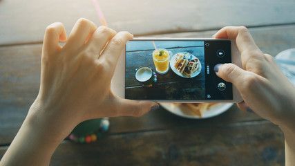 closeup hand holding phone shooting food photograph
