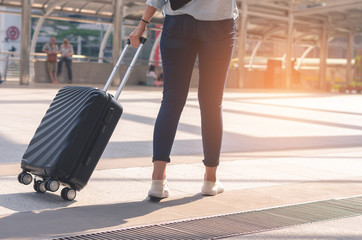 backside of beautiful traveler girl holding and pull luggage walking on concrete floor at outdoor in the city with sunlight and go to travel planing in vacation time concept.