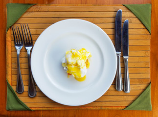 Egg Benedict plated on a bamboo tray with silverware.