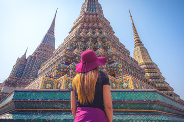 rear view of a women tourist looking up at Pagoda in Wat Pho temple in Bangkok in day , Thailand , Southeast Asia .
