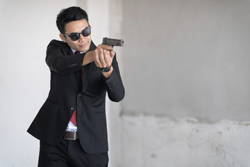 Handsome man with sunglass is aim the gun. Selective focus at his face.