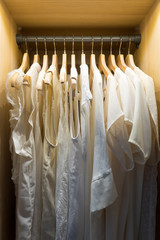 Picture taken straight into a wardrobe. White summer blouses and sweaters on hangers. Wooden wardrobe with lightning.