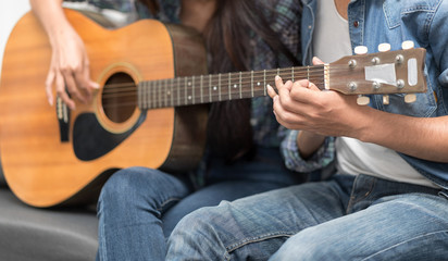 In selective focus of Young beautiful couple resting at home and playing guitar.Woman learning to playing a song.