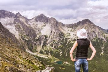 Kobieta na szczycie góry, podziwiająca górskie krajobrazy. Góry Tatry pejzaż ze szczytu.