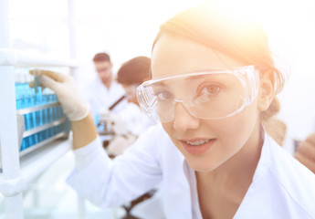 Young woman scientist in protective glasses holding test tubes