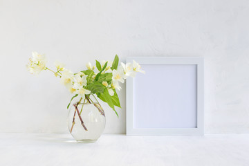 Mockup with a white frame and white jasmine flowers