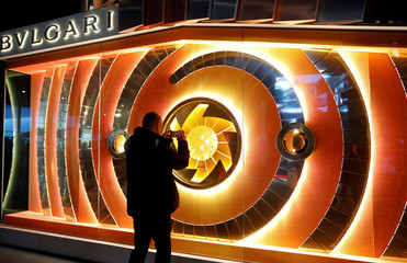 A visitor takes pictures of a display window of Bulgari at the Baselworld watch and jewellery fair in Basel