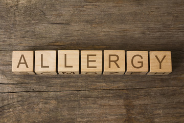 Allergy word written on wooden cubes on wooden background