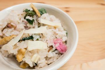 Japanese food, okawa (sticky rice) with vegetables and sakura flower.