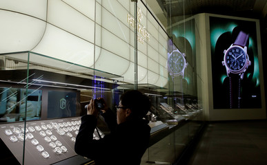 A visitor takes pictures of a display window of Swiss watch manufacturer Patek Philippe at the Baselworld watch and jewellery fair in Basel