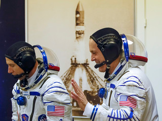 The International Space Station (ISS) crew members astronauts Drew Feustel and Ricky Arnold of the U.S walk after donning space suits shortly before their launch at the Baikonur Cosmodrome