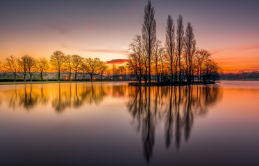 Pontefract Park Lake and reflection on water at sunrise, West Yorkshire, UK