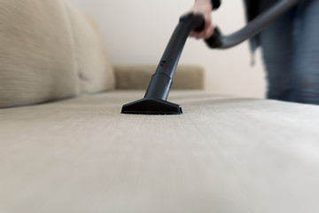 Woman cleaning the sofa, couch with vacuum cleaner