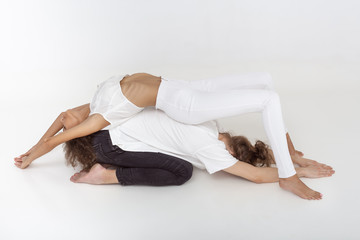 Young mixed-race athletic couple practicing acroyoga. Balancing in pair indoors on white background. Young Afro-American woman and Caucasian man laying meditating with closed eyes together in yoga