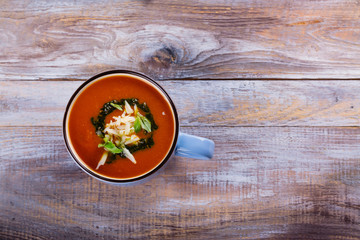 Tomato soup with pesto sauce and parmesan cheese in a ceramic cup