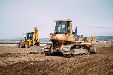 Industrial motor grader and backhoe excavator on highway construction site