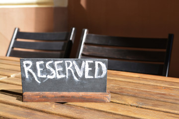 Reserved table. The reserved logo. Booking badge. Wooden reservation sign. Reserved table in the restaurant. Hungry. Busy