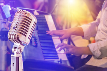 Close up retro microphone with musician playing keyboard synthesizer on band in night concert background