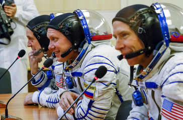 The International Space Station (ISS) crew members astronauts Arnold, Feustel of the U.S and crewmate Artemyev of Russia speak with their families after donning space suits shortly before the launch at the Baikonur Cosmodrome