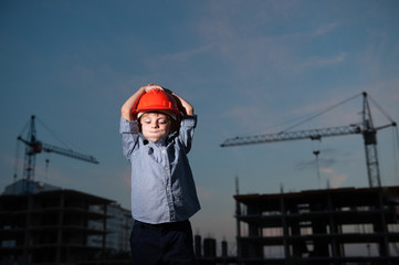 boy blows his cheeks clutching his head in helmet against background of building cranes and construction buildings at dusk