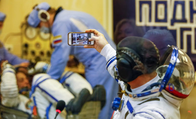 The International Space Station (ISS) crew member astronaut Drew Feustel takes a selfie as he talks with his family after donning his space suit shortly before the launch at the Baikonur Cosmodrome