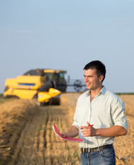 Engineer with notebook and combine harvester in field
