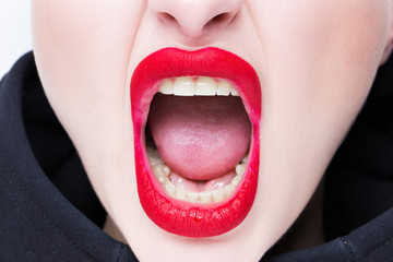 Mouth of a girl with red lips. Emotion screams. Close-up