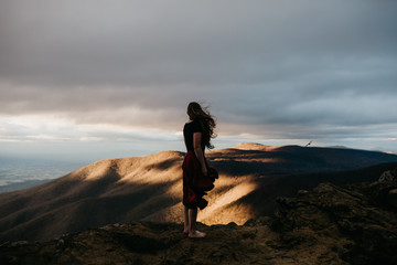 Young Woman Standing on Top of A Mountain at Sunset