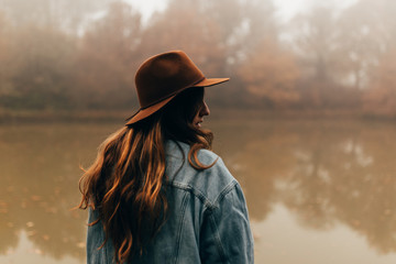 Young woman in hat standing by pond on foggy day