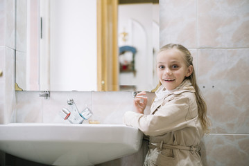 Cheerful girl in coat at sink